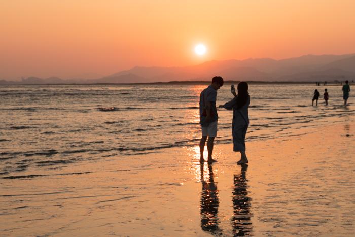 釜山多大浦ビーチの夕日とデート中の若者