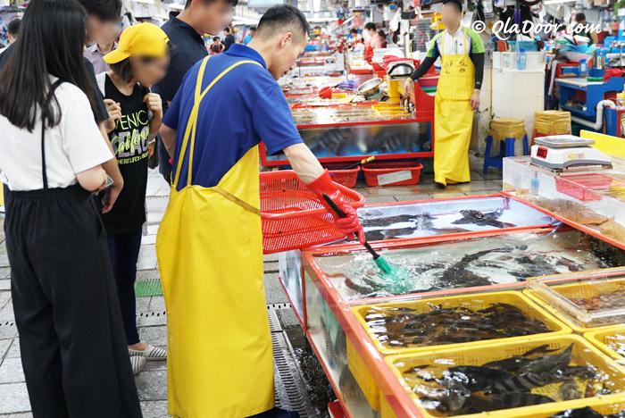 釜山チャガルチ市場で交渉中の観光客